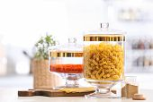 Jars with foodstuff on wooden table in modern kitchen poster