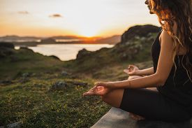Healthy Lifestyle And Yoga Concept. Close-up Hands. Woman Do Yoga Outdoors At Sunrise In Lotus Posit