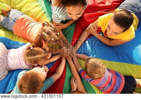 Group Of Children With Teachers Holding Hands Together On Rainbow Playground Parachute, Top View. Su