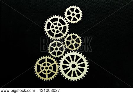 Gear Wheels Or Wooden Wheel Gears With A Dark Background