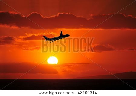 Airliner Flying Into Tropical Sunset