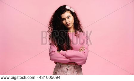 Dissatisfied Woman Standing With Crossed Arms And Looking At Camera Isolated On Pink