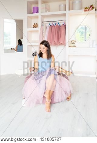 Young Joyful Charming Brunette Lady In Pink Tutu-skirt Sitting On Cozy Ottoman In Dressing Room, Hol
