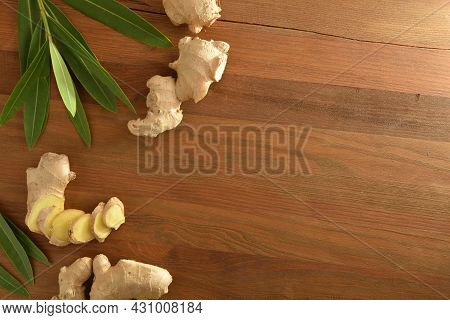 Ginger Root As A Product For Healing Purposes With Sliced Portions And Leaves On Wooden Table. Top V