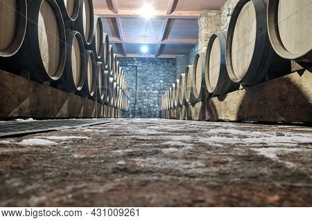 Row Of Oak Barrels In A Dry Cool Wine Cellar In Basement