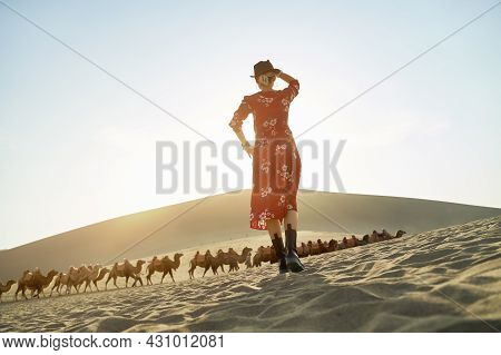 Rear View Of Asian Woman In Red Dress Standing In Desert Looking At View With Caravan Of Camels And