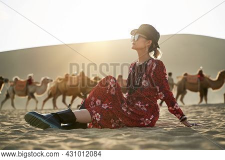Asian Woman In Red Dress Sitting In Desert Looking At View With Caravan Of Camels And Huge Sand Dune