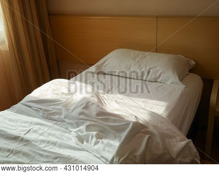 Unmade Bed With Crumpled Duvet, Bed Sheet And Pillow At The Hotel In The Morning