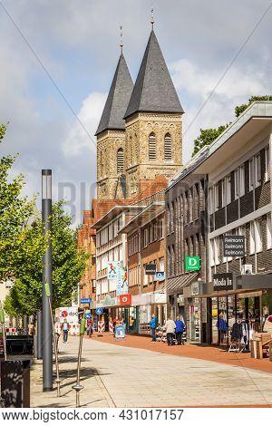 Gronau, Germany - August 26, 2021: Streetscene Downtown Gronau With Shops And St Agatha Church In No