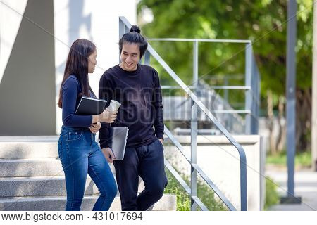Students Walk The Stairways On Campus, A Couple Walking Down Into The Ground For Extra Education.