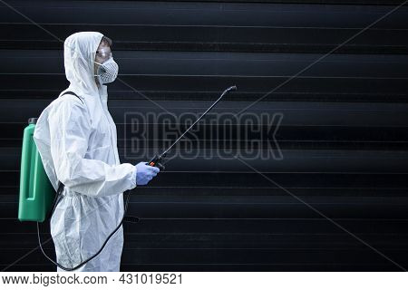 Person In White Chemical Protection Suit Holding Sprayer With Disinfectant Chemicals To Stop Spreadi