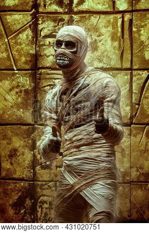 Emotional Halloween mummy against the background of a wall with ancient Egyptian hieroglyphs. Halloween. Ancient Egyptian mythology. Invitation for a party.
