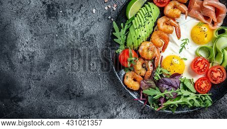 Ketogenic Breakfast. Keto Low Carb Salmon, Grilled Shrimps, Prawns, Fried Eggs, Fresh Salad, Tomatoe
