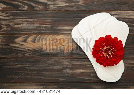 White Sanitary Pad, Hygiene Protection On A Brown Background. Gynecological Menstrual Cycle. A Rose
