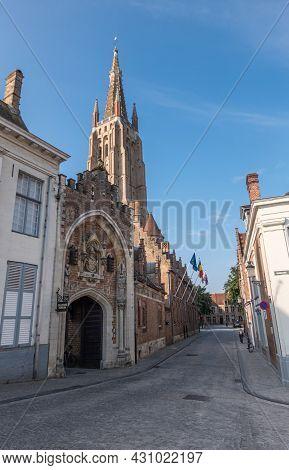 Brugge, Flanders, Belgium - August 4, 2021: Sunlit Onze Lieve Vrouw Cathedral Tower Under Blue Sky B