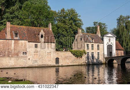 Brugge, Flanders, Belgium - August 4, 2021: Sunlit Beguinage Entrance And Long Canal Facing Wall And
