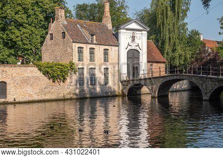 Brugge, Flanders, Belgium - August 4, 2021: Sunlit Beguinage Entrance, Canal Bridge And House Under