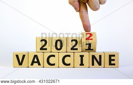 Symbol Of Covid-19 Vaccine In 2022. Doctor Turns A Wooden Cube And Changes Words 'vaccine 2021' To '