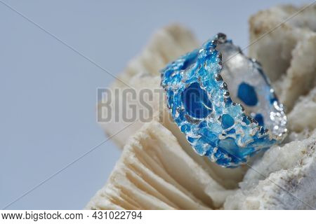 Macro Shot Of Handmade Silver Metal Ring With Blue Enamel On Top Arranged On Seashell Isolated Over