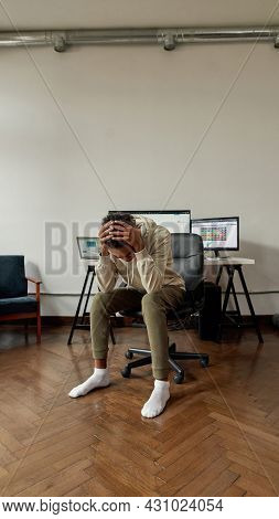 Hopeless Young Guy, Trader Holding Head In Despair After Stock Market Business Failure, Sitting At D