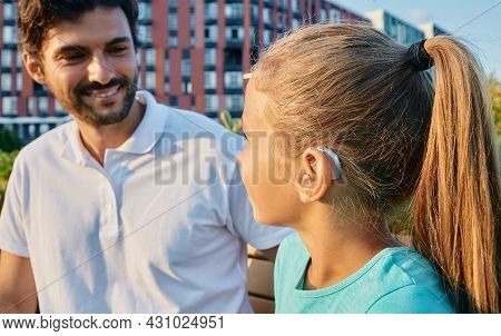 Positive Female Child With A Hearing Impairment Uses A Hearing Aid To Communicate With Her Father Ou