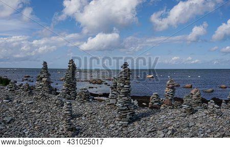 A Rocky Beach With Many Stone Cairns And A Calm Ocean In The Background