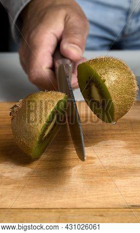 Cutting A Kiwi. Man's Hand With A Knife Cutting A Kiwi On A Wooden Board