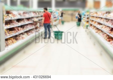Blurred Aisle And Shelves In Supermarket With Customers. Refrigerator With Meat Products And Sousage