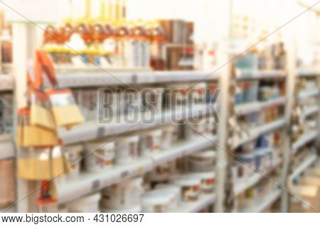 Blurred Image Of Shelves With Interior Paints, Varnish, Brushes In Store Of Building Materials As Sh