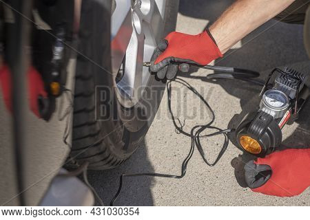 Tire Pump Inflating Car Wheel. Tyre Inflator In Male Hands.