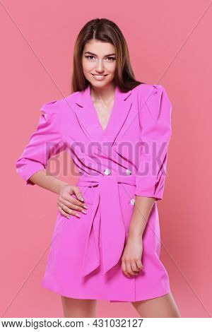 Beauty, fashion portrait. Charming young woman in fashionable fuchsia jacket smiling at camera. Studio portrait on a pink background.