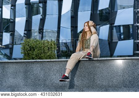 Beautiful Caucasian Girl With Dreadlocks Sitting On The Parapet And Looking Into The Distance. Again