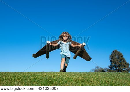 Boy Child With Wings At Sky Imagines A Pilot And Dreams Of Flying. Kids Adventure, Children Freedom