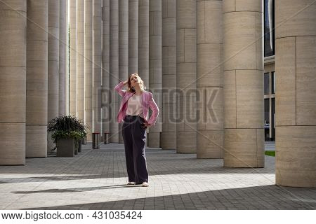Young Elegant Beautiful Blonde Millennial With Long Hair In Pink Clothes Stands And Looks Up In The
