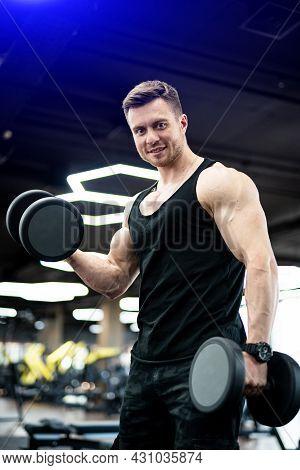 Bodybuilder Training His Biceps. Strong Handsome Man Working Hard In Gym.