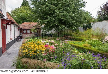Brugge, Flanders, Belgium - August 4, 2021: Green Garden With Flowers Of All Colors As Courtyard Of