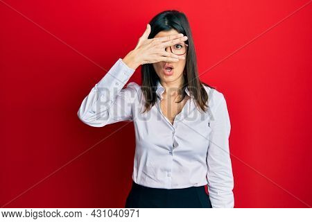 Young hispanic woman wearing business shirt and glasses peeking in shock covering face and eyes with hand, looking through fingers with embarrassed expression.