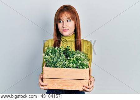 Redhead young woman holding wooden plant pot smiling looking to the side and staring away thinking.