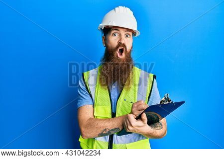 Redhead man with long beard wearing safety helmet holding clipboard afraid and shocked with surprise and amazed expression, fear and excited face.