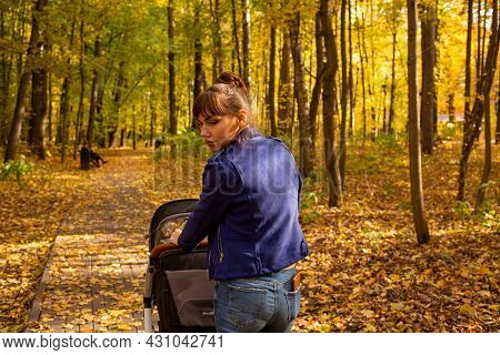 Young Mother Goes With A Stroller In The Autumn Park. A One-year-old Infant Is Sleeping In A Carriag