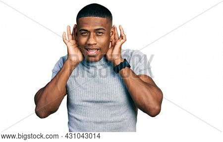 Young black man wearing casual t shirt trying to hear both hands on ear gesture, curious for gossip. hearing problem, deaf