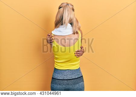 Beautiful blonde sports woman wearing workout outfit hugging oneself happy and positive from backwards. self love and self care