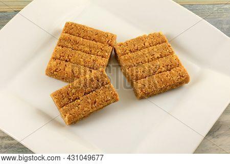 Crunchy Peanut Brittle Cake Bars On White Snack Dessert Plate