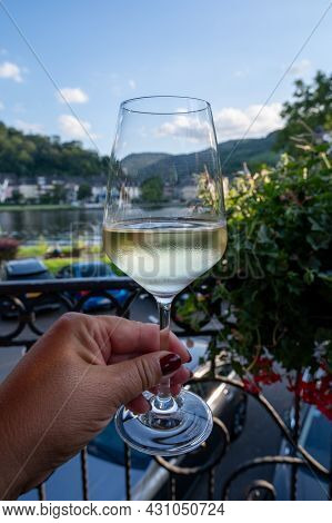 Hand Holding Glass Of White Quality Riesling Wine Served On Outdoor Terrace In Mosel Wine Region Wit