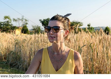 Closeup Of 40 Years Old Brazilian Woman With Sunglasses In A Wheat Field.