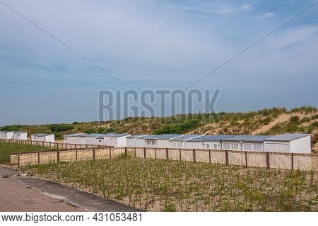 Knokke-heist, Flanders, Belgium - August 5, 2021: Row Of White Cabins Set In Dunes And Shielded From