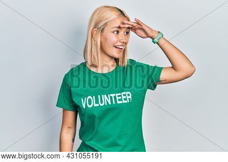 Beautiful blonde woman wearing volunteer t shirt very happy and smiling looking far away with hand over head. searching concept.