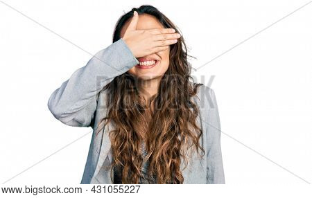 Young hispanic girl wearing business clothes and glasses smiling and laughing with hand on face covering eyes for surprise. blind concept.