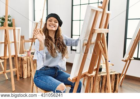 Young hispanic artist woman painting on canvas at art studio waiving saying hello happy and smiling, friendly welcome gesture