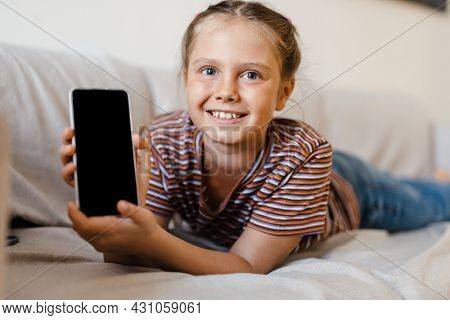 White preteen girl smiling and showing cellphone while lying on couch at home